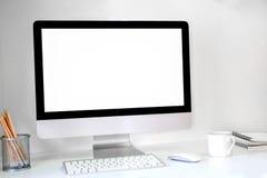 Kreativer Hippie-Desktop mit leerem weißem Bildschirm, Kaffeetasse und anderen Einzelteilen auf weißem Ziegelsteinhintergrund Lizenzfreies Stockfoto