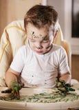 Kreativer kleiner Junge, der mit Fingerfarbe spielt Stockfotografie