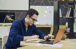 Kreativer Mann, der Anmerkungen an seinem Arbeitsplatz macht Lizenzfreie Stockfotos