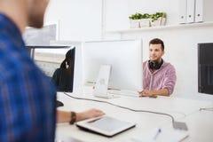 Kreativer Mann mit Kopfhörern und Computer Stockfotografie
