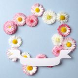 Kreativer Plan mit Frühlingsblumen und festlichem Papierband Jahrestagskonzept Flache Lagezusammensetzung Draufsicht, obenliegend lizenzfreie stockbilder