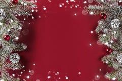Kreativer Planrahmen gemacht von den Weihnachtstannenzweigen, Kiefernkegel, Geschenke, rote Dekoration auf rotem Hintergrund lizenzfreies stockfoto
