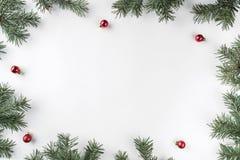Kreativer Rahmen gemacht von den Weihnachtstannenzweigen auf weißem Hintergrund mit roter Dekoration, Kiefernkegel stockfotografie