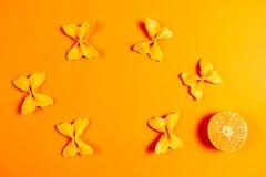 Kreativer Sommerplan gemacht von den Klementinen und von farbigem Teigwarengrieß papillon auf Leuchtorangehintergrund Minimales K lizenzfreie stockbilder