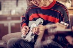 Kreativer Student, der seine Gitarre hält und Melodie komponiert stockfotos