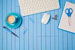 Kreatives Arbeitsplatzkonzept mit Tastatur, Kaffeetasse und Notizbuch auf hölzerner blauer Tabelle Lizenzfreies Stockfoto