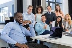 Kreatives Büro Afroamerikaner-Geschäftsmann-Leading Meeting Ins, Chef Using Laptop Computer im Vordergrund über Geschäft stockfoto