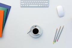 Kreatives Büro-helle Tabelle mit Farbzeitschriften und Bleistifte Computer und Kaffeetasse Stockfoto