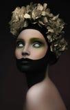 Kreatives dunkles Make-up mit Gold blüht auf ihrem Kopf Stockfotografie
