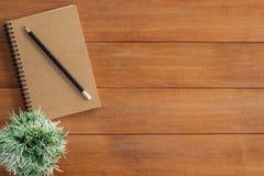 Kreatives Ebenenlagefoto des Arbeitsplatzschreibtisches Schreibtischholztischhintergrund mit Spott herauf Notizbücher und Bleisti lizenzfreies stockbild