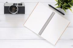 Kreatives Ebenenlagefoto des Arbeitsplatzschreibtisches Weißer Schreibtischholztischhintergrund mit Spott herauf Notizbücher und  stockfoto