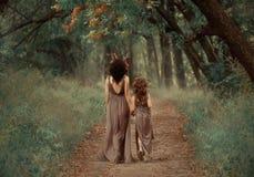 Kreatives Familienfoto der brunette Mutter und der blonden Tochter, Faun halten Hände und gehen in den Wald entlang tief stockbilder