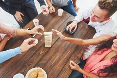 Kreatives Foto der Draufsicht von den Freunden, die am Holztisch sitzen Freunde, die Spaß beim Spielen des Brettspiels haben Lizenzfreies Stockfoto