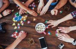 Kreatives Foto der Draufsicht von den Freunden, die am Holztisch sitzen Spaß beim Spielen des Brettspiels haben Stockbild
