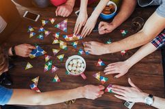 Kreatives Foto der Draufsicht von den Freunden, die am Holztisch sitzen Spaß beim Spielen des Brettspiels haben Lizenzfreie Stockfotografie
