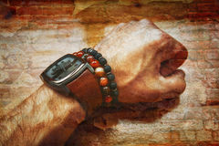 Kreatives Foto - Doppelbelichtung - die Mann ` s Hand, die Armbanduhren und die Armbänder mit Steinen Stockfotografie