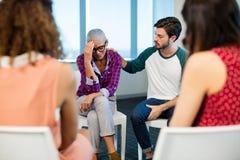 Kreatives Geschäftsteam, das umgekippten Kollegen tröstet stockbild