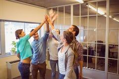 Kreatives Geschäftsteam, das ihre Hände anhebt Stockbild