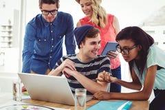Kreatives Geschäftsteam, das stark zusammen an Laptop arbeitet Lizenzfreies Stockbild
