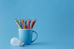 Kreatives Ideenkonzept der Kunst, Bleistifte im Becher und Glühlampe Stockfotografie