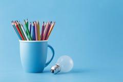 Kreatives Ideenkonzept der Kunst, Bleistifte im Becher und Glühlampe Stockfoto