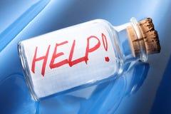 Ein künstlerisches Konzept einer Flasche mit einer Mitteilung HILFE! Lizenzfreie Stockfotografie