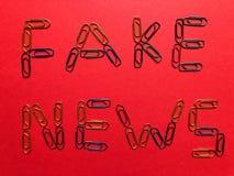 Kreatives Konzept, gefälschte Nachrichten auf Rot stockfotografie