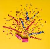 Kreatives Konzept mit festlichem Dekor auf Gelb Konfettiherzen und Sterne, Bänder, Geschenkbox Stockfotografie