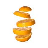 Kreatives Konzept mit fliegender Orange Geschnittene Orange lokalisiert auf weißem Hintergrund Lizenzfreie Stockfotos