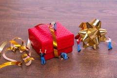 Kreatives Konzept mit Miniaturleuten und einer Geschenkbox auf einem hölzernen Hintergrund Lizenzfreies Stockfoto