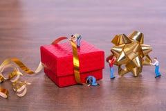 Kreatives Konzept mit Miniaturleuten und einer Geschenkbox auf einem hölzernen Hintergrund Prozessverpackungsgeschenke Lizenzfreie Stockfotografie