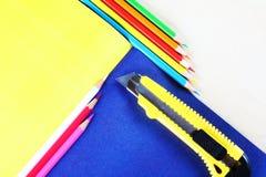 Kreatives Konzept von den mehrfarbigen Bleistiften, die auf buntem shee liegen Stockfotografie