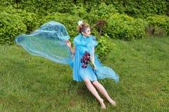 Kreatives Make-up und Schönheitsthema: schönes Mädchenmodell mit Fantasiemake-up auf Gesicht in einem transparenten Kleid mit Blu lizenzfreies stockbild