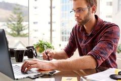 Kreatives Sitzen des jungen erwachsener Mannesunternehmers beim Arbeiten Lizenzfreie Stockbilder