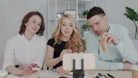 Kreatives stilvolles Team von Leuten kommen on-line-Sendung von einem Smartphone auf den Markt Sie sind lächelnd wellenartig bewe stock video footage