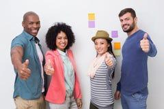 Kreatives Team, das oben Daumen im Büro gestikuliert lizenzfreie stockfotos