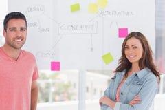 Kreatives Team, das vor whiteboard steht Stockfotos