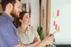Kreatives Team mit Aufklebern auf Glas im Büro Stockfotos