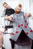 Kreatives ungewöhnliches blondes Mädchen und rothaariger Mann in der Designer-Kleidung und in den Zöpfen auf ihren Köpfen Lizenzfreie Stockbilder