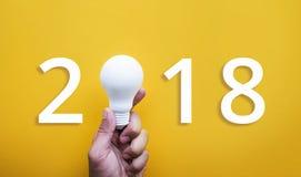 Kreativitätskonzept mit 2018 Ideen mit der menschlichen Hand, die Glühlampe hält Stockbild