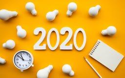 Kreativitet av 2020 begrepp med gruppen av lightbulb- och textnumret på bakgrund för pastellfärgad färg Aff?rsl?sning Kapacitet a arkivbild