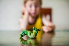Kreativitet för barn` s barnlera sculpts Den gulliga pysen gjuter från plasticine på tabellen Arkivbilder