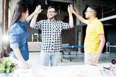 Kreatywnie biznes drużyna Wysocy Pięć w biurze obraz stock