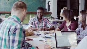Kreatywnie biznes drużyny spotkanie w nowożytnym biurze Mieszana biegowa grupa młodzi ludzie dyskutuje uruchomienie pomysły, śmia zbiory wideo