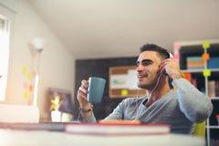 Kreatywnie biznesmena słuchająca muzyka przy biurkiem Obrazy Royalty Free