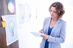 Kreatywnie bizneswoman bierze notatkę na schowku Obrazy Royalty Free