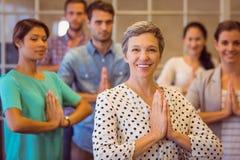 Kreatywnie bizneswomanu modlenie z jej drużynową pracą Zdjęcie Stock