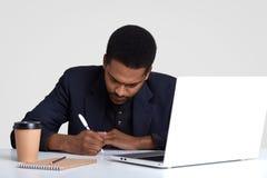 Kreatywnie copywriter pisze puszków pomysłach, siedzi przed rozpieczętowanym laptopem, otaczającym z notepad, dispoasable filiżan obraz royalty free
