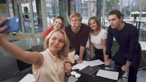 Kreatywnie drużyna bierze selfie na smartphone po uzupełniać pomyślnego projekt w nowożytnym centrum lub przydział zbiory wideo