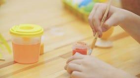 Kreatywnie dziewczyna jest mieszająca wodę w słoju i mieszająca Dziewczyna wybierał zieleń malować Wielkanocny pojęcie, zgłasza d zbiory wideo